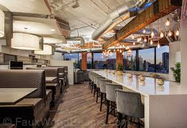 a rustic beam with dripping light bulbs beautifully accents the bar in this high rise beams lighting