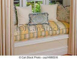 a seating area in a bay window with decorative pillows and cushions in a window seat bay window seat cushion