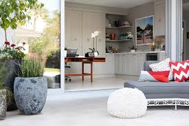 folding patio doors open to reveal a home office fitted with a wooden mid century modern office desk centered in front of wall to wall light gray paneled bi fold doors home office