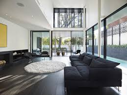furniture spectacular black sectional sofa design idea for living room with round white rug black hardwood floor tile and glass windows comfy sectional sofa black white rug home