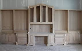 the section also features the bumped up staggered depths with decorative round corners and furniture wrap lumber atop scroll toe kick inserts built in study furniture
