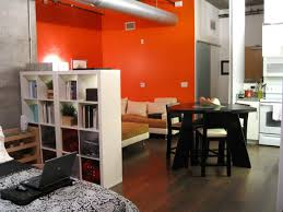 ideas studio apartment furniture  ideas beautiful style living room decorating studio apartments with orange wall paint color and calm white bookcase also wooden floor and modern sofa set also handsome dinning room and cool white cush