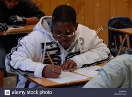 african american boy in th grade english class works on writing african american boy in 9th grade english class works on writing skills while developing a personal essay at dunbar high school