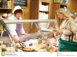 female s assistant serving customer in delicatessen royalty female s assistant serving customer in delicatessen