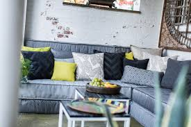 gallery outdoor living wall featuring:  outdoor sofa with grey cushions covered in many grey pillows and some green pillows to add