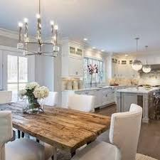 open kitchen design farmhouse: l shaped kitchen with island and eat in table at back also cabinets with open glass tops wood table floor plant are the only things with color