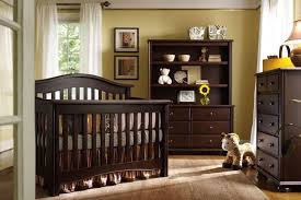 dark wood arched back crib and matching dressers stand in this yellow nursery over hardwood flooring baby nursery yellow grey gender neutral