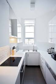 small u shaped kitchen design: minimalist white decor flooded with light brings black elements forward through contrast