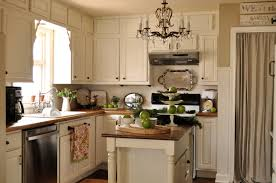 painted kitchen cabinets vintage cream: complete tiny open kitchen with small island and white painted kitchen cabinets on laminate flooring
