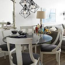 black and white dining table set: round black dining table with white dining chairs