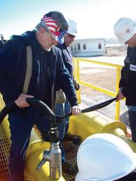 a worker lowers the gamajet into a frac tank for cleaning oil tank cleaning equipment