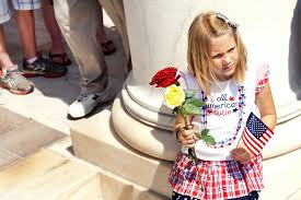 u s department of defense photo essay a girl holds a flag and flowers during the memorial day observance ceremony at the amphitheatre