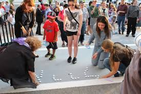 students and community members lighting candles at the memorial vigil on july 1 2014 alter lighting