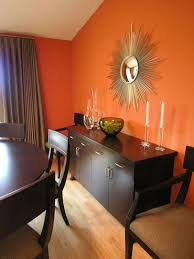 dining room khaki tone: vibrant dining the dark wood dining set and buffet are a sweet complement to pumpkin orange walls in this chic dining room a gold sunburst mirror echoes