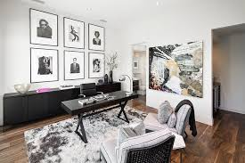 a collection of black and white framed photographs and wall add to the neutral color scheme black and white home office