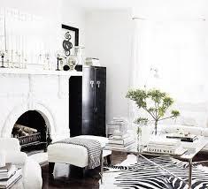 monelle totah white black chic living room design cow hide zebra rug mirror glass x base silver coffee table upholstered white bench wood floors chic zebra print rug
