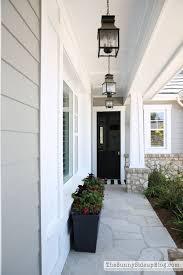 craftsman style custom home with stonework and gray shingles facade beach style balcony helius lighting group