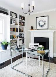 chic office features a reed small chandelier hangs over a glass and stainless steel desk placed dead center of the room in front of a fireplace chic office desk