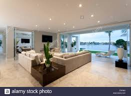 beautiful living room with open doors to a yard viewing a big lake beautiful open living room