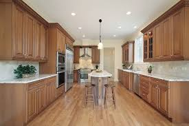 long kitchen with counters and cabinets lining three walls very narrow and long island runs spacious eat kitchen