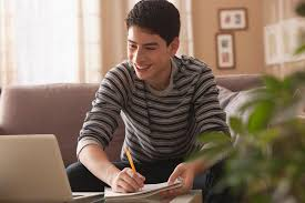 A boy working on homework on the couch  US News   World Report