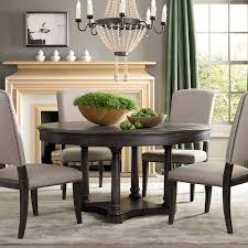 black kitchen dining sets: luxury crystal chandelier above round black kitchen table paired with brown dining chairs near stoned fireplace