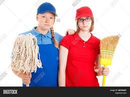 two serious looking teenage girls dressed in uniforms for menial two serious looking teenage girls dressed in uniforms for menial jobs and holding a broom