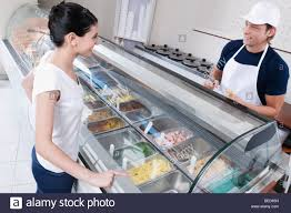 s clerk in an ice cream parlor stock photo royalty image s clerk attending a customer in an ice cream parlor stock photo