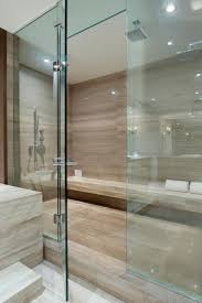 spa bathroom showers: glass doors open to an enormous walk in shower boasting neutral marble floors and walls bathroom idealsspa