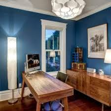 transitional office with royal blue walls and wood furniture blue home offices
