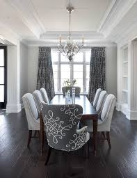 transitional dining chair sch: gray dining room features a tray ceiling accented with a satin nickel and glass chandelier illuminating