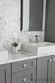 bathroom features gray shaker vanity: formica calacatta marble laminate countertop hexagon mosaic marble backsplash and chelse gray vanity in ensuite bathroom with raised sinks by kylie m