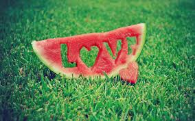 A watermelon slice has the word LOVE carved out of it and a heart next to it on the grass