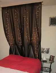 white string lights behind a black dark colored sheer curtain to creat a modern black fabric lighting