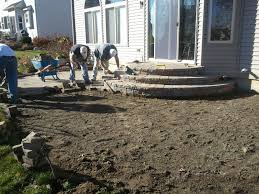 stone patio installation: we approached this brick paver repair and restoration with a complete re installation of the paving stone patio due to the severe pitch back to the home