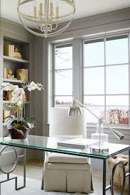 chic home office features a silver sphere chandelier illuminating a glass top desk with geometric chic home office features