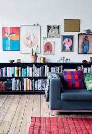 living room with a colorful gallery wall a bookshelf and a gray sofa casual living room lots