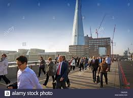 commuters walking to work over london bridge the shard commuters walking to work over london bridge the shard building in the background