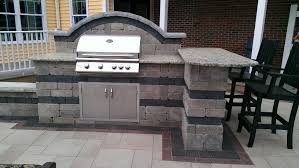 patio outdoor stone kitchen bar: outdoor kitchen and bar with stainless steel grill and doors on a paver patio designed and