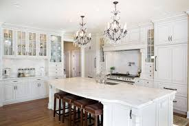 beautiful white kitchen cabinets: luxury kitchen with white glass face cabinets carrara marble counter island and two chandeliers
