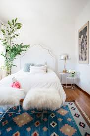 feminine bedroom furniture bed: feminine bedroom with a white upholstered headboard and a blue area rug