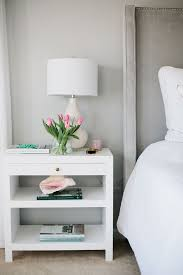 ideas bedside tables pinterest night:  as a backdrop for a gray velvet headboard with silver nailhead trim dressed in soft white bedding situated next to white lacquer nightstand with brass