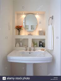 downlighting above oval mirror in alcove above white pedestal basin in modern bathroom bathroom down lighting