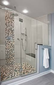 spa bathroom showers: the frameless glass in this contemporary shower in doylestown pa really shows off the simple cobble waterfall and rain shower head