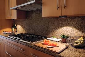 wooden cabinets and bright led under cabinet lighting near the granite backsplash and the countertop cabinet lighting backsplash