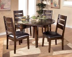 room simple dining sets: brilliant dining room simple small dining room arrangements ideas with round dining table with leaf and  wooden chairs with black leather cushions on