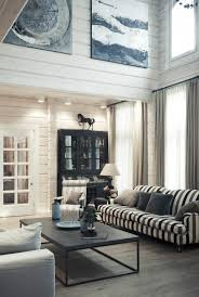 carefully chosen pieces of artwork take the plainness off the white washed wooden walls black and white striped furniture