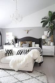 neutral bedroom with crystal chandelier button tufted chaise black and white accents and leather black and white bedroom furniture