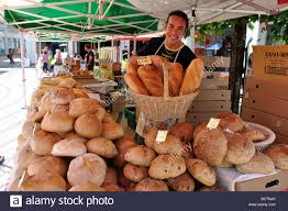 stall owner holding b loaves continental food market the stall owner holding b loaves continental food market the piazza wimbledon greater london england united kingdom