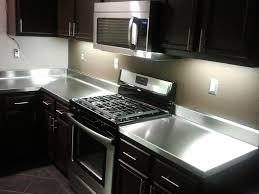 black and stainless kitchen light up the stainless steel countertops on dark countertop under wooden floating cabinets and grey backsplash
